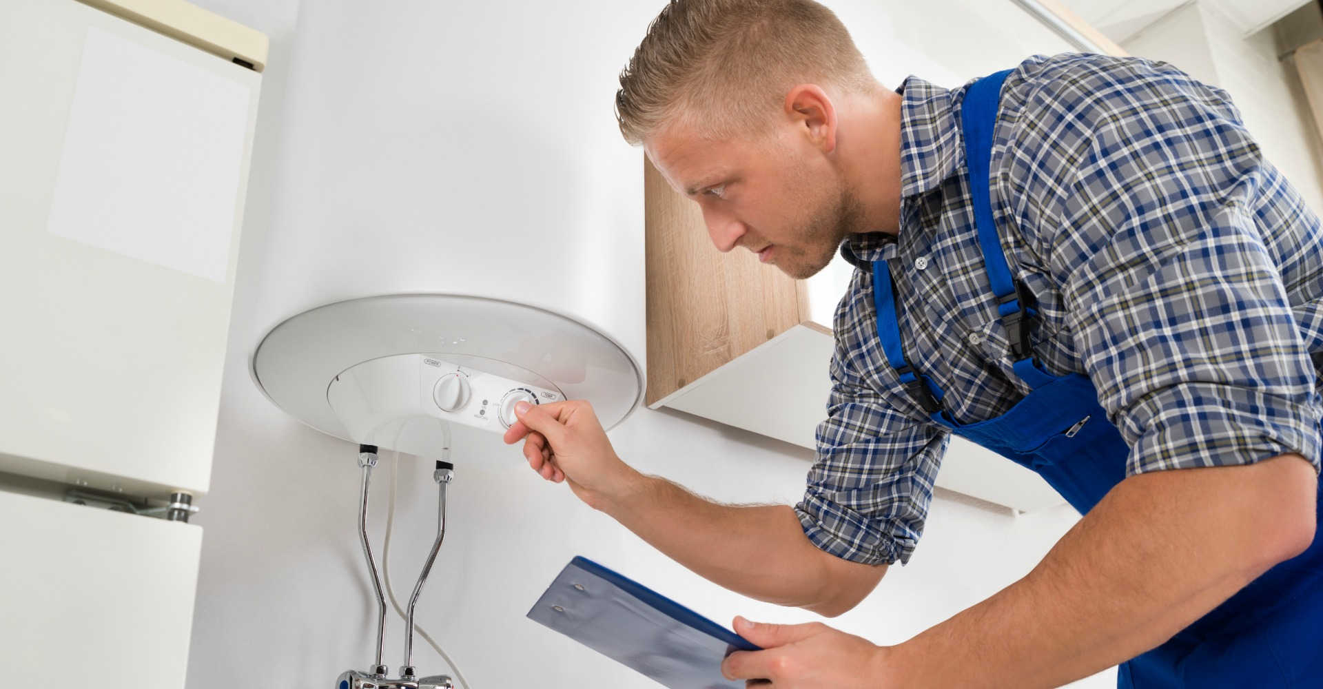 Male Worker With Clipboard Adjusting Temperature Of Water Heater